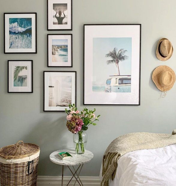 Gallery wall con poster spiaggia in cornici color noce